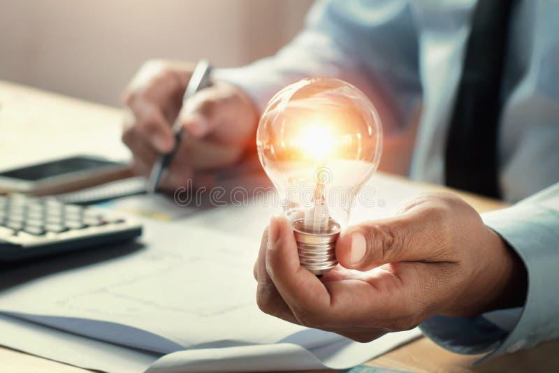 拿着电灯泡的商人手在办公室 概念想法保存 免版税图库摄影