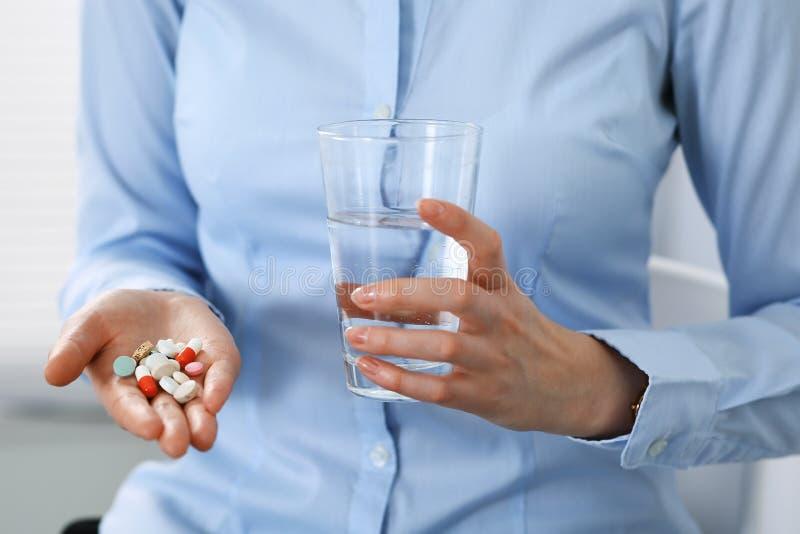 拿着药片和杯水,手特写镜头的年轻未知的妇女  医学和医疗保健概念 免版税库存照片
