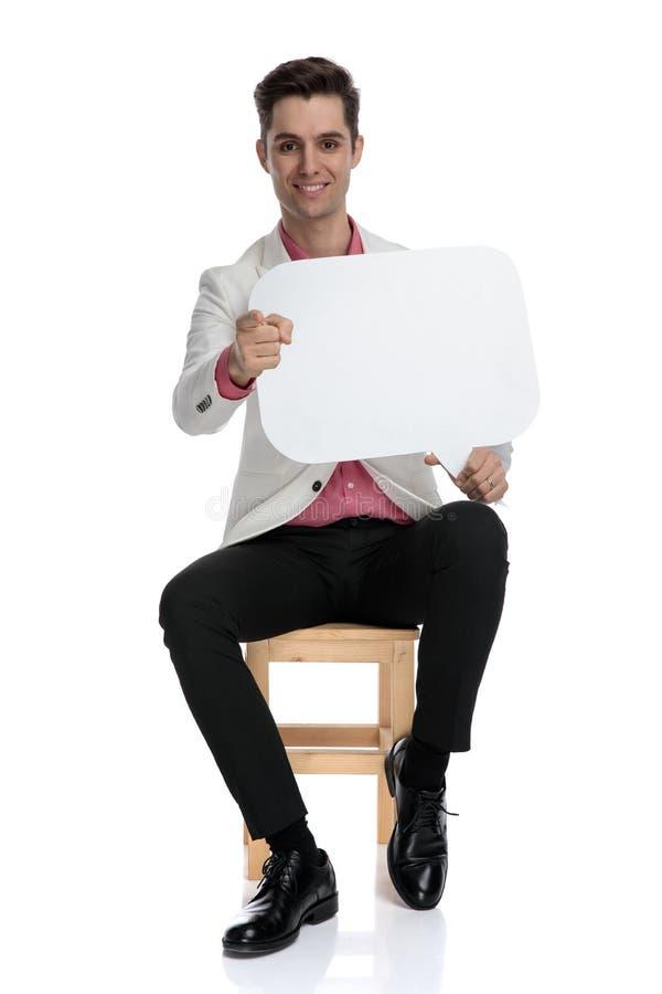 拿着讲话泡影的微笑的聪明的偶然人指向手指 免版税库存图片
