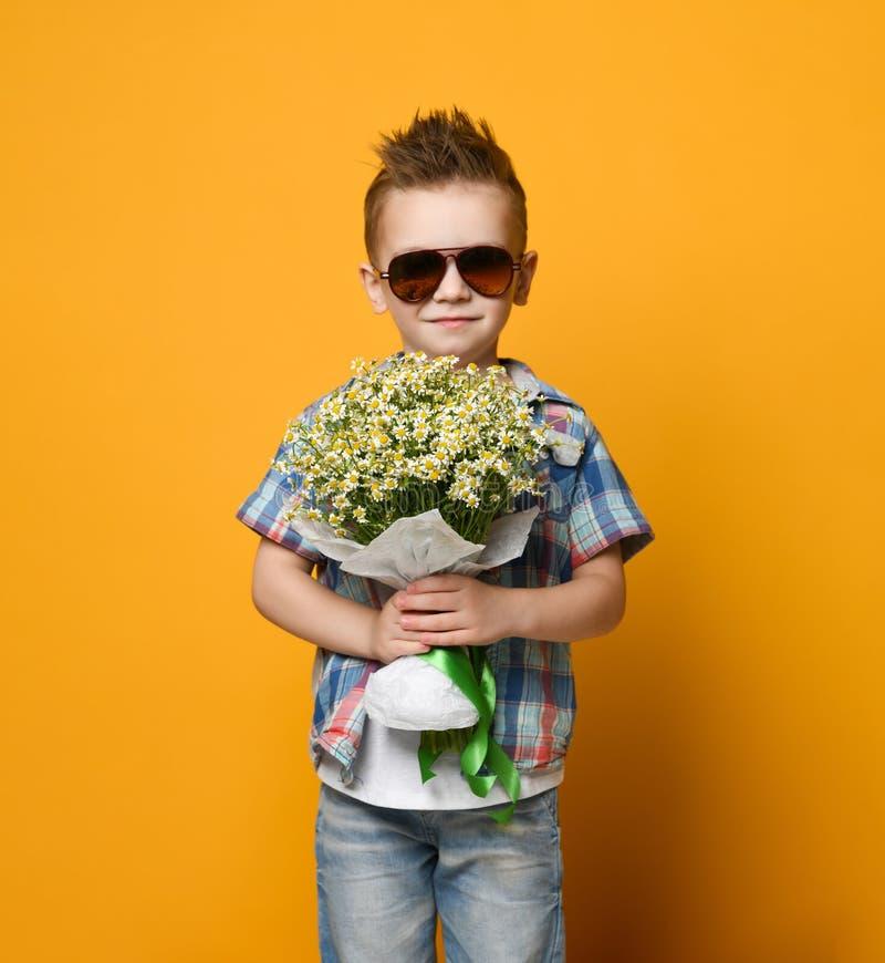 拿着花束的逗人喜爱的小男孩 免版税库存图片