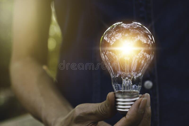 拿着能量力量概念的手电灯泡在自然背景中 库存图片