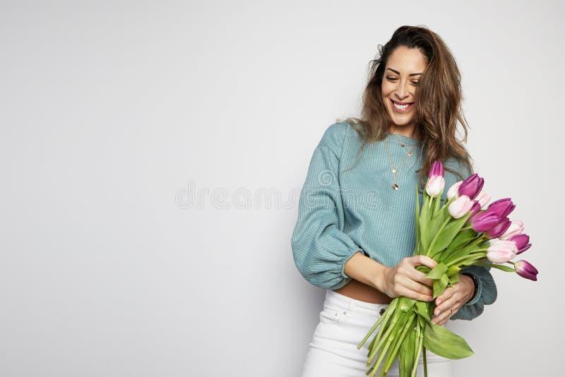 拿着色的郁金香花束的一可爱的年轻女人的画象被隔绝在灰色背景 复制浆糊空间 免版税图库摄影