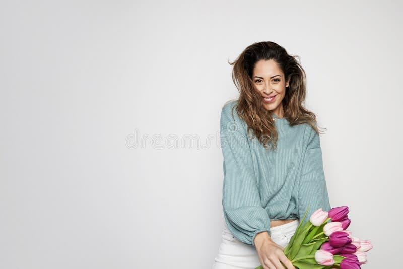 拿着色的郁金香花束的一微笑的年轻女人的画象被隔绝在灰色背景 复制浆糊空间 免版税图库摄影