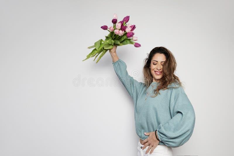 拿着色的郁金香花束的一美丽的年轻女人的画象被隔绝在灰色背景 复制浆糊空间 免版税库存照片