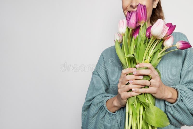 拿着色的郁金香花束的一英俊的年轻女人的画象被隔绝在灰色背景 复制浆糊空间 免版税库存图片
