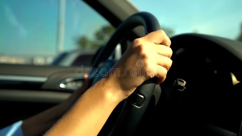 拿着黑方向盘,女孩的少年手驾驶汽车不定地 免版税库存图片