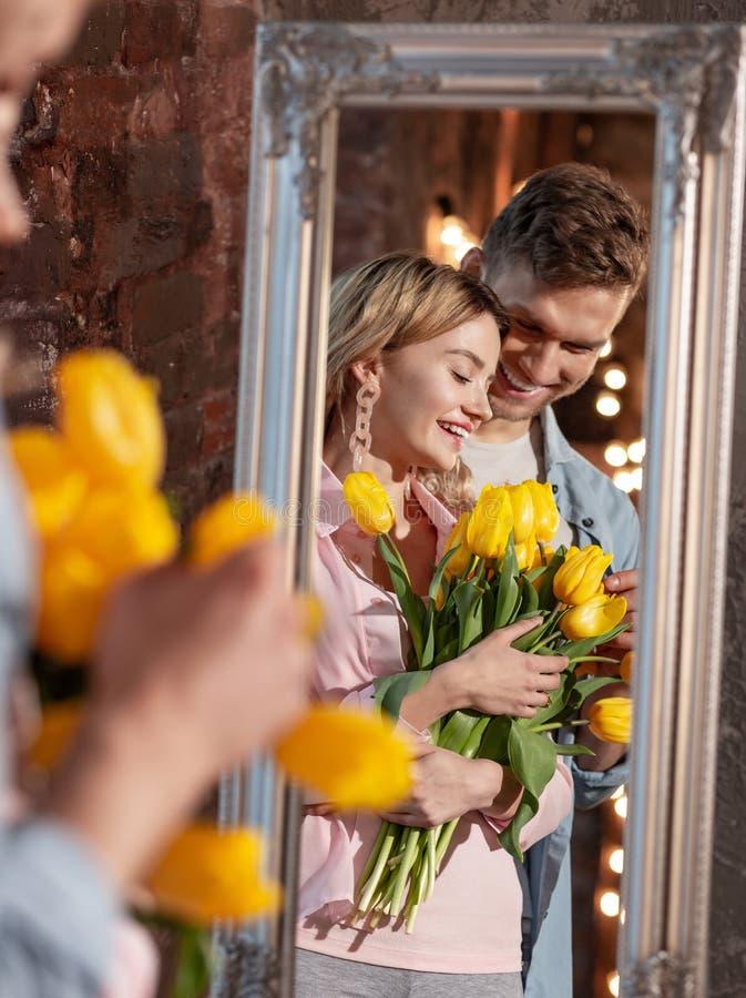 拿着黄色郁金香的放光的美女站立在丈夫附近 库存照片
