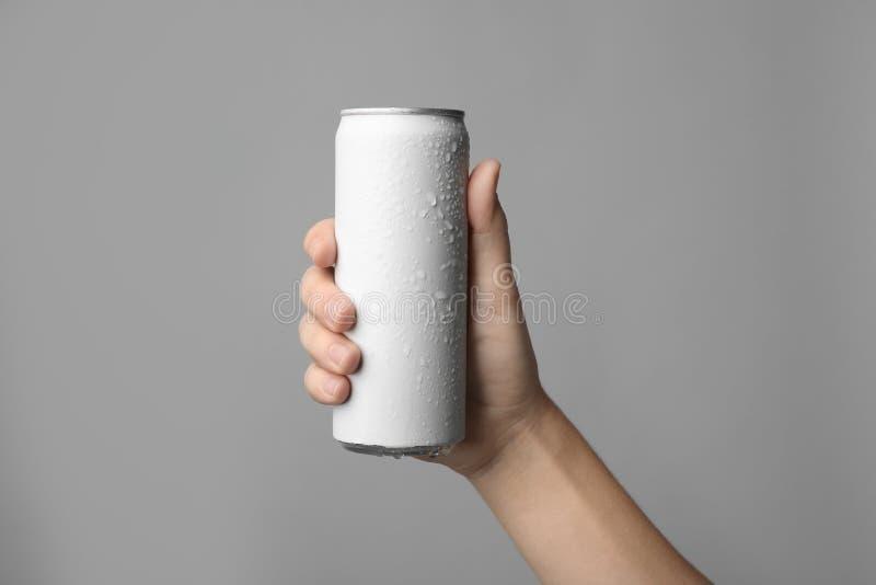 拿着铝罐用在灰色背景,特写镜头的饮料的妇女 免版税库存图片