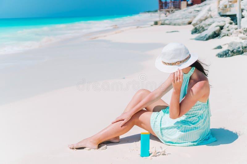 拿着suncream的美丽的年轻女人说谎在海滩 免版税库存图片