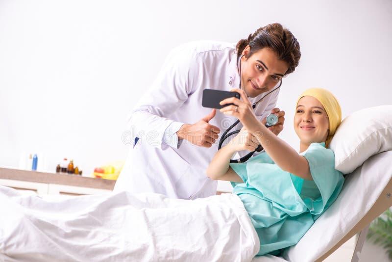 拜访女性肿瘤学患者的年轻英俊的医生 图库摄影
