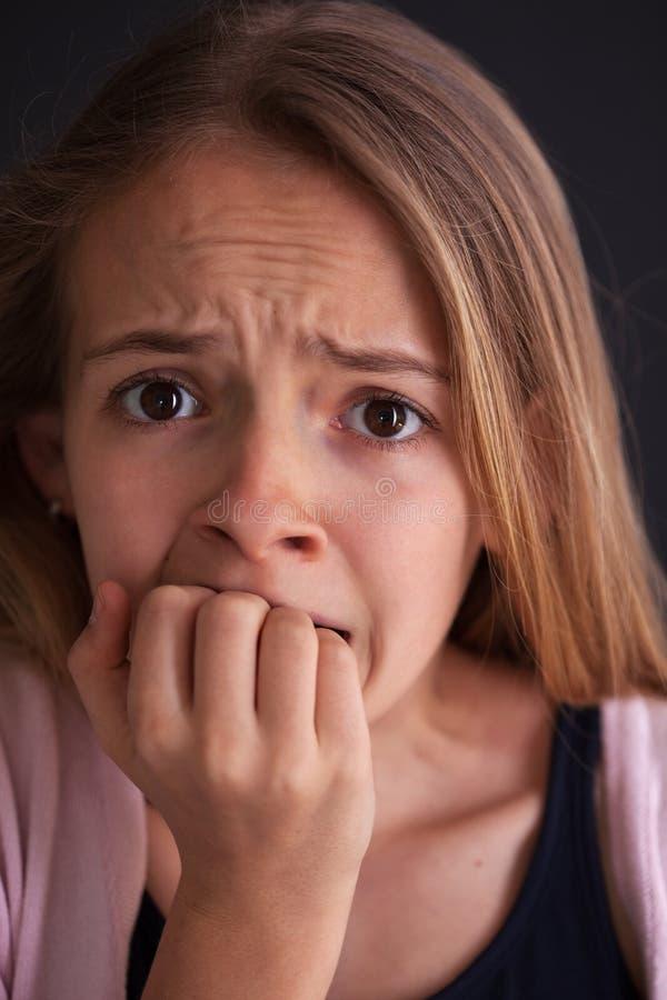 担心的少年女孩叮咬她的钉子-接近画象 免版税库存照片