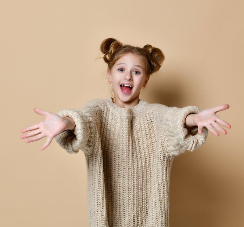 拉扯往照相机的逗人喜爱的矮小的女性女孩手,微笑从幸福,要拥抱与您在米黄背景 库存照片
