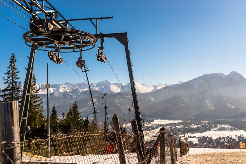 拉扯绳索和暂停的椅子在背景太脱拉山的滑雪电缆车,可看见的大,驱动轮的机制 免版税库存照片