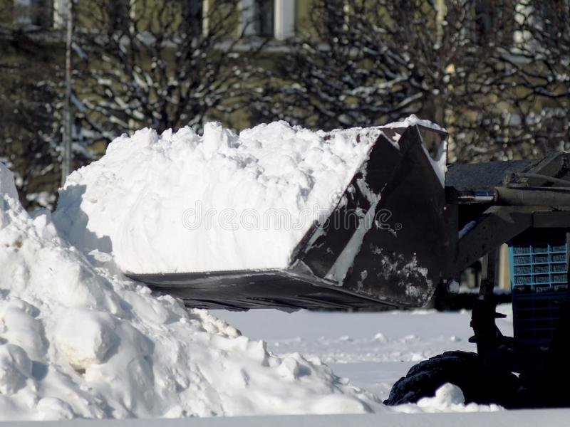 拖拉机在大雪以后扫清道路 免版税库存图片