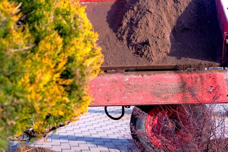 拖拉机在城市倾吐从桶的地球在床上 免版税图库摄影