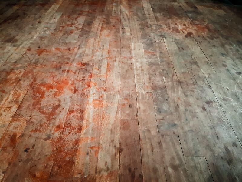 拖着脚走路的肮脏的硬木地板,显示类似血液-被放弃的房子的红色污点,可怕恐怖场面背景 免版税库存图片