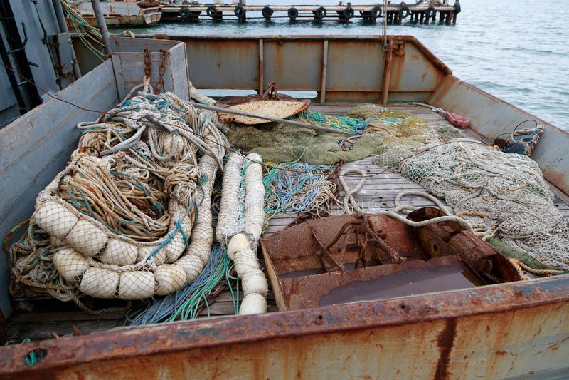 拖网,远洋板,鱼网在一个小钓鱼的围网渔船的渔场甲板说谎 库存照片