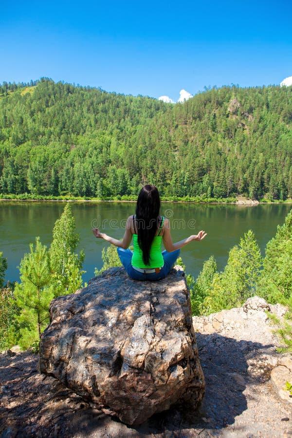 思考在莲花姿势的妇女做瑜伽在山顶部在岩石 免版税库存照片
