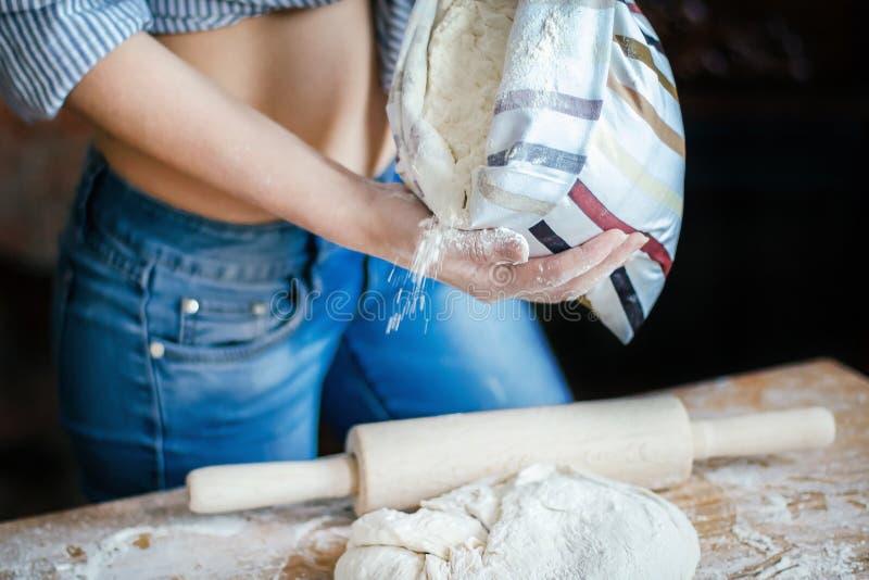 性感女孩腹部、面团、面粉袋子和滚针特写镜头  性感的年轻女人在厨房里准备面团 免版税库存照片