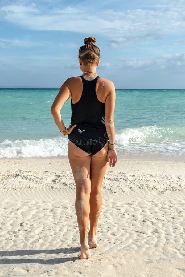 性感的年轻白种人妇女背面图放松在沙子离开的海滩的闭合的泳装的 图库摄影