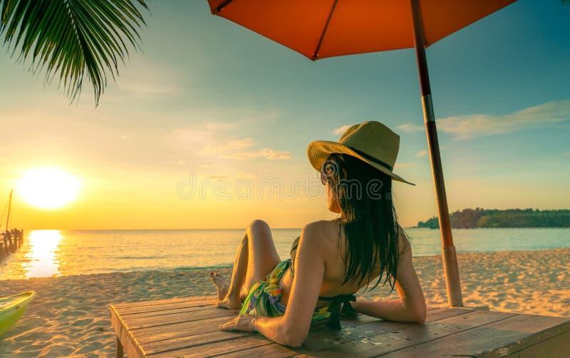 性感,享用并且放松说谎和晒日光浴在sunbed的女服比基尼泳装在沙滩在天堂热带海岛海滩 免版税库存照片