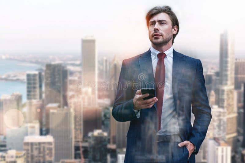 总是可利用 在经典穿戴的英俊和时髦的商人使用他的智能手机,当站立反对时 免版税库存图片