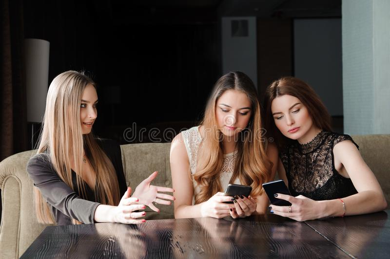 总是连接,互联网瘾,看他们的智能手机,人脉概念的咖啡馆的少女 库存照片