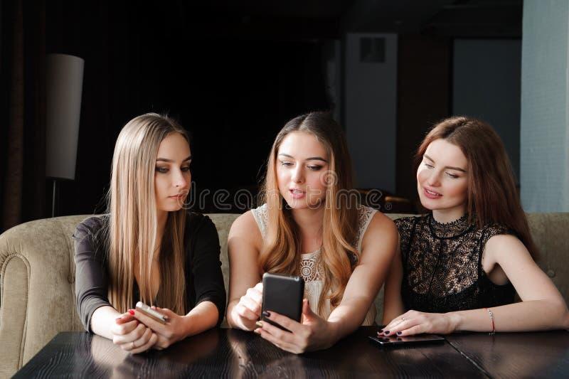总是连接,互联网瘾,看他们的智能手机,人脉概念的咖啡馆的少女 免版税图库摄影