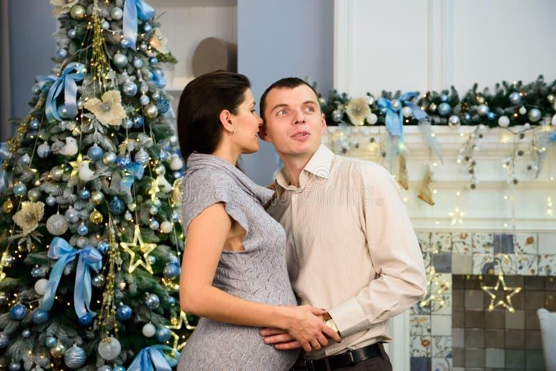 怀孕、寒假和人概念-有丈夫的愉快的怀孕的妻子在家圣诞节的 年轻家庭 免版税库存照片