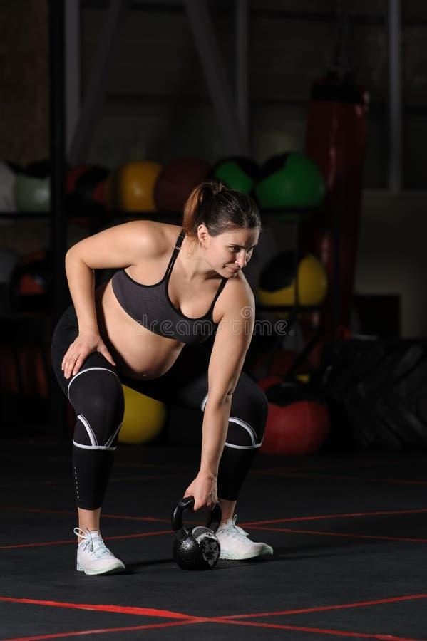 怀孕女运动员做垂悬kettlebell清洗和按 库存照片