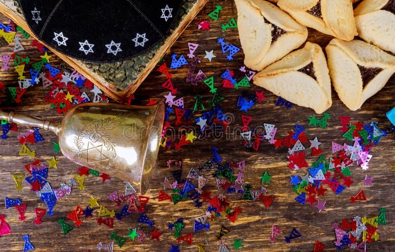 普珥节庆祝犹太狂欢节假日hamantaschen与木桌和洁净酒的曲奇饼 免版税库存图片