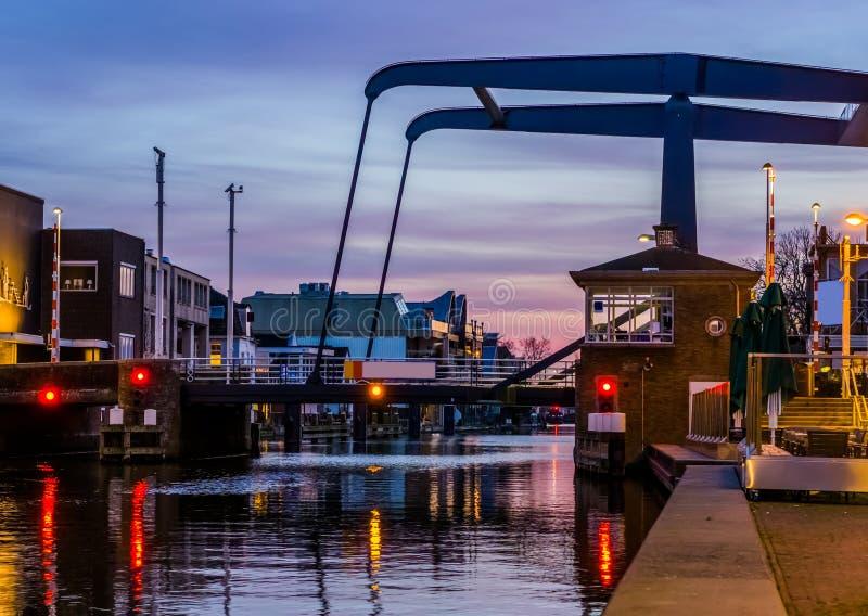 普遍的城市桥梁alphensebrug在莱茵河畔阿尔芬,荷兰,在日落的美好的水风景 库存图片