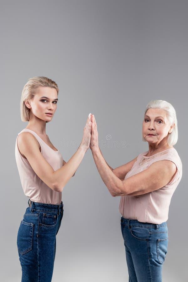断然的举手的少女和老灰发的妇女 免版税库存照片