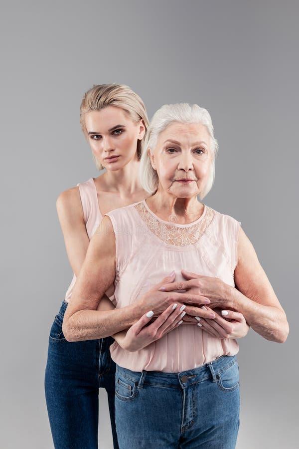 支持她的老微弱的母亲的柔和的白肤金发的少女 免版税库存照片