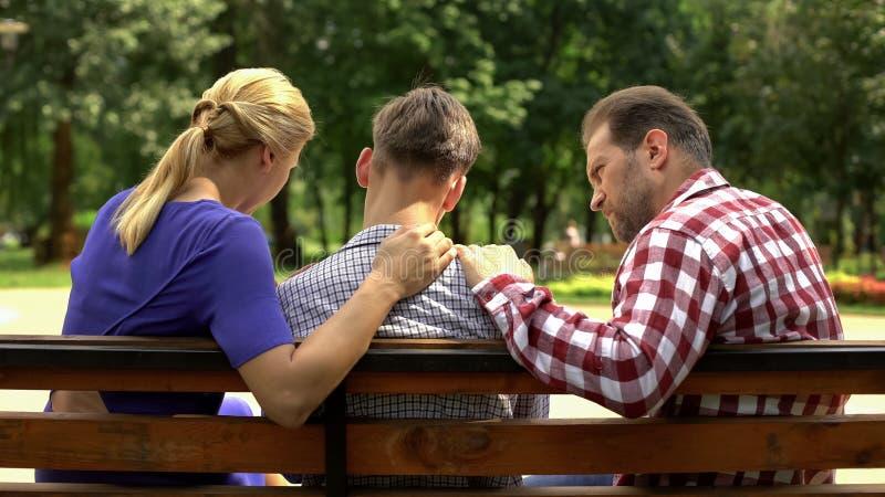 支持哀伤的青少年的儿子的关心的母亲和爸爸坐长凳在公园,危机 免版税库存图片