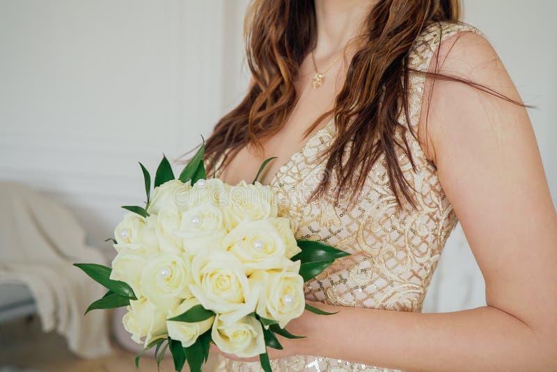 新娘庄稼照片美丽的金黄礼服的有白玫瑰婚礼花束的在手上,关闭 库存图片