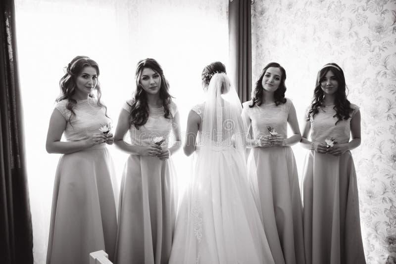 新娘站立对照相机 女傧相举行花束在手上 他们在窗口前面停留 免版税库存照片