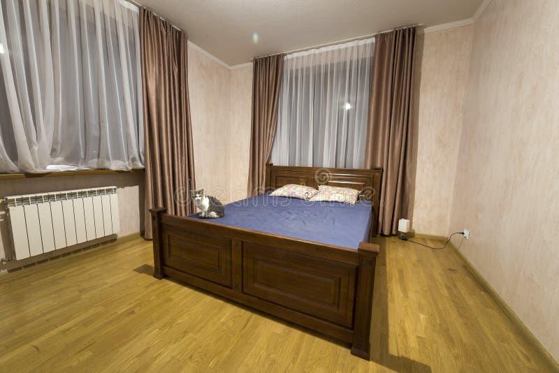 新的宽敞在白色和棕色口气的卧室室内设计 木地板和舒适的双人床,在宽的精密帷幕 库存图片