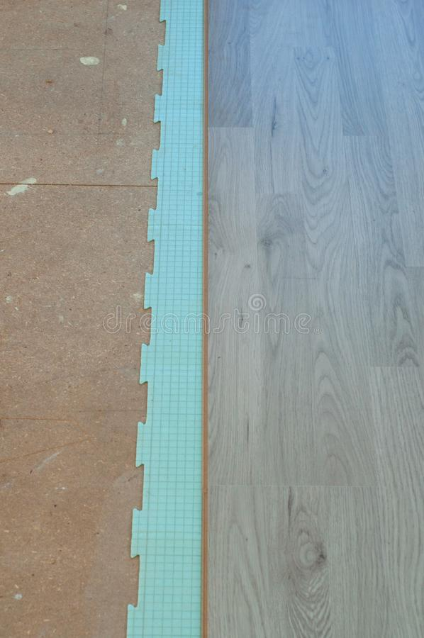 新的层压制品的地板的Istalation,使用隔绝的合理的资料 免版税库存图片