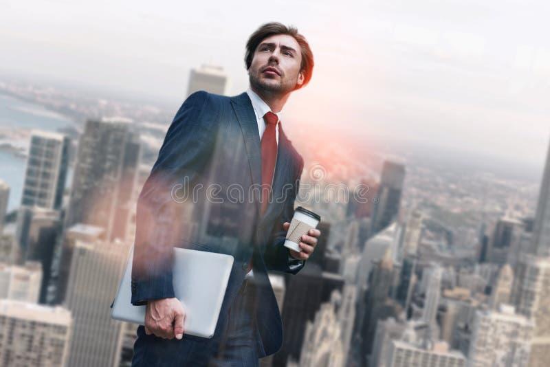 新的工作日 英俊的年轻商人藏品膝上型计算机和咖啡,当站立反对早晨都市风景时 库存照片