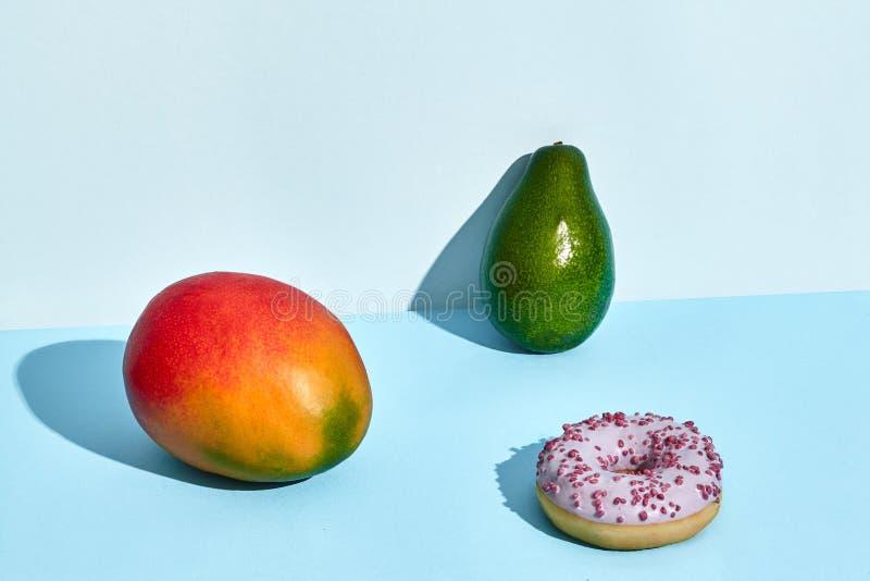 新鲜水果的构成和甜点、多福饼芒果和鲕梨在两色背景 图库摄影