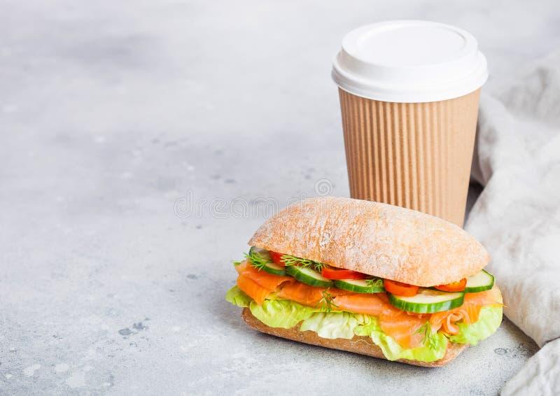 新鲜的健康三文鱼三明治用莴苣和黄瓜与纸咖啡在白色石背景 早餐快餐 空间 库存图片