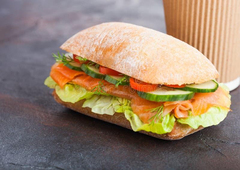 新鲜的健康三文鱼三明治用莴苣和黄瓜与纸咖啡在黑石背景 早餐快餐 库存图片