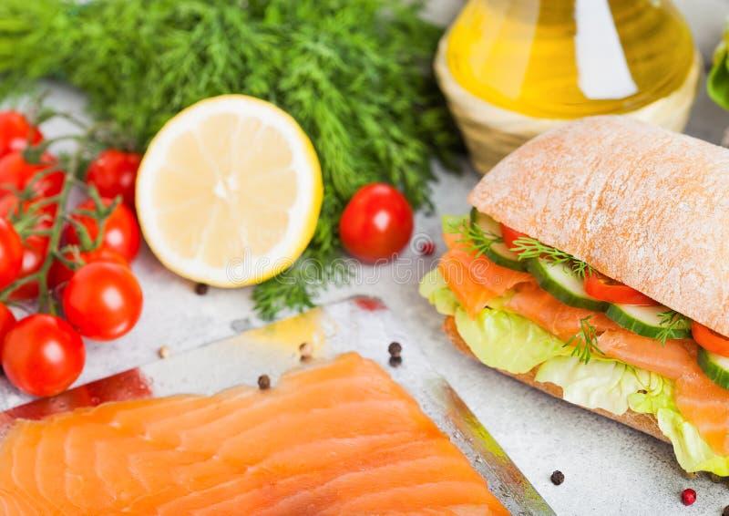 新鲜的健康三文鱼三明治用莴苣和黄瓜在板材在白色石背景 早餐快餐 新鲜的蕃茄, 免版税库存照片