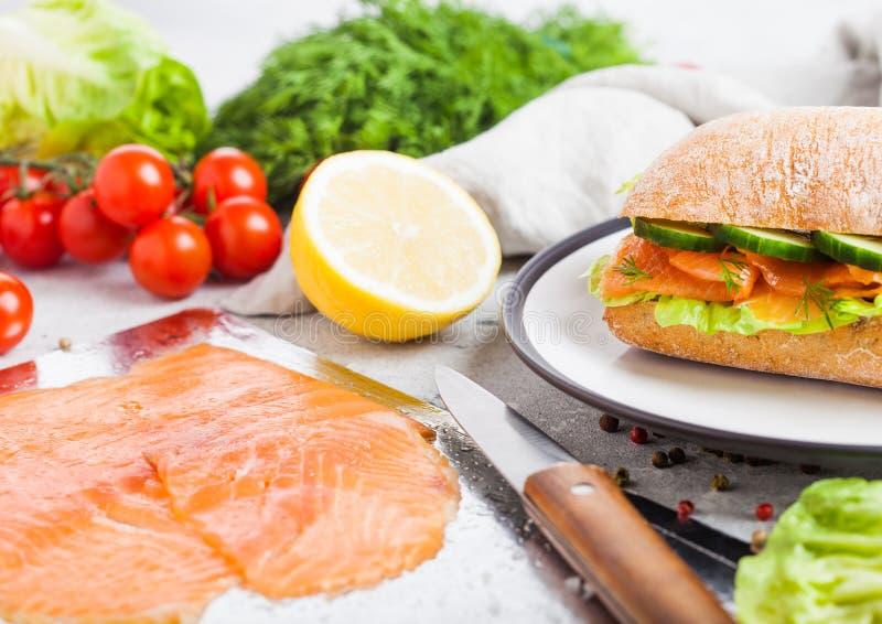 新鲜的健康三文鱼三明治用莴苣和黄瓜在板材在白色石背景 早餐快餐 新鲜的蕃茄, 免版税图库摄影