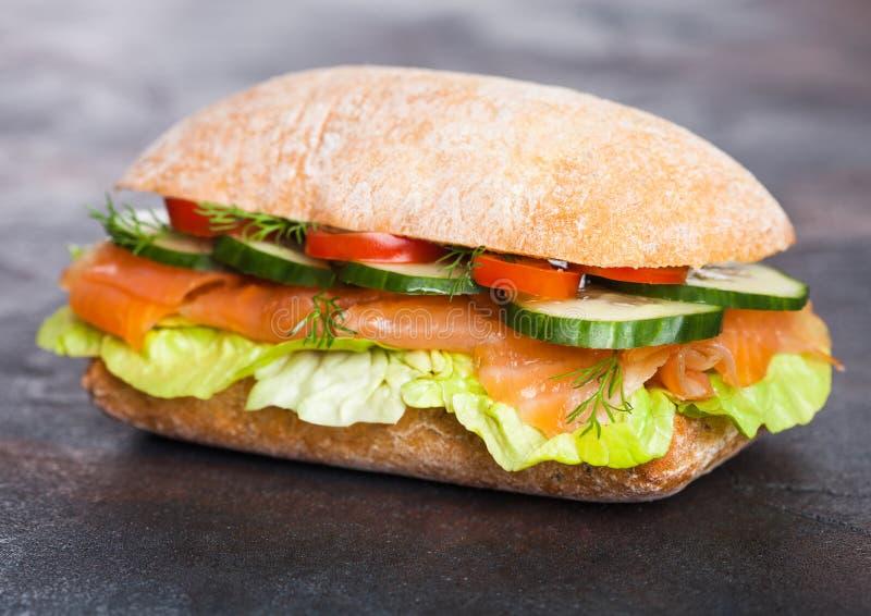 新鲜的健康三文鱼三明治用莴苣和黄瓜在黑石背景 早餐快餐 饮食食物 免版税库存照片