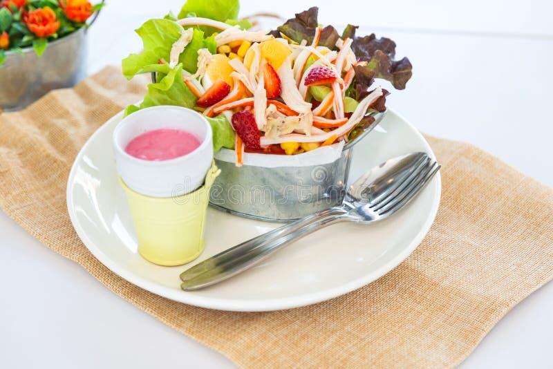 新鲜的沙拉的关闭与煮沸的鸡和stawberry在白色背景的桶 库存照片