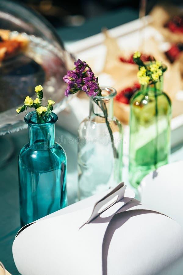 新鲜的矮小的多彩多姿的statice萨利姆或补血草属在户外蓝色,白色和绿色瓶的sinuatum花 装饰  免版税库存照片