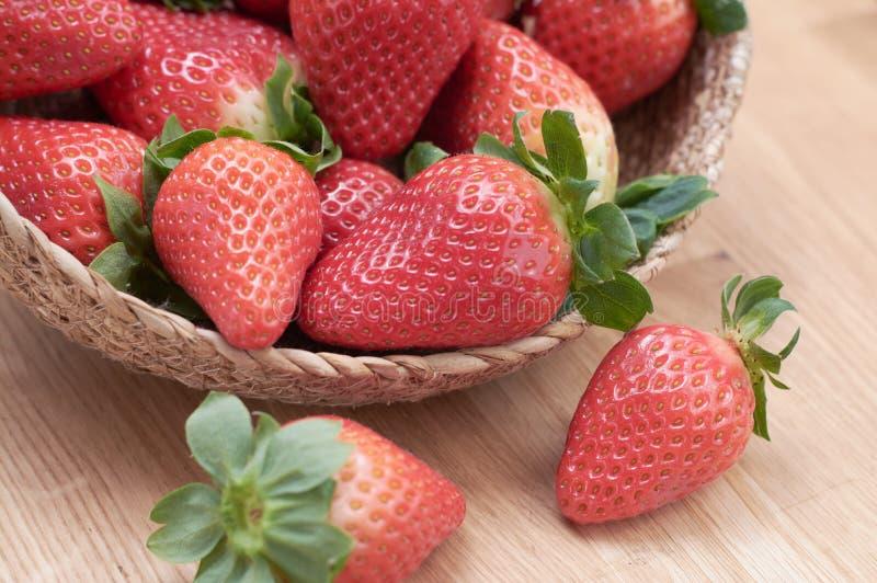 新鲜的草莓的关闭有在篮子的自然木背景 库存照片