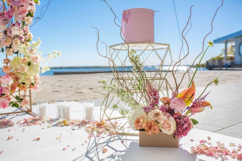 新鲜的花瓣在地板上说谎在一个装饰的婚姻的曲拱和白色蜡烛旁边 与鲜花的事件装饰 库存照片